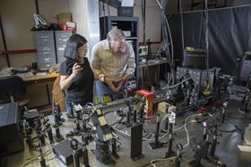 Sarah Li (left) and Valy Vardeny (right) of the Department of Physics & Astronomy at the University of Utah study the ultrafast laser they used to prepare and measure the direction of the electron spin of hybrid perovskite methyl-ammonium lead iodine. Photo: University of Utah.