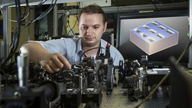 Sergey Kruk in front of a diagram of the metamaterial structure. Photo: Stuart Hay, ANU.