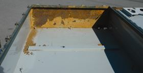 Figure 3: Coating on the internal surface of a delaminated box; the exposed sheet steel is severely corroded.