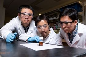 Georgia Tech researchers (left to right) Yanjie He, Zhiqun Lin and Jaehan Jung demonstrate how magnetic nanorods fabricated with their new technique are attracted to a magnet. Image: Rob Felt, Georgia Tech.