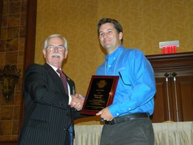 NASF president Tony Revier (left) presents Award of Merit to stand-in for Barry Lee Cohen.