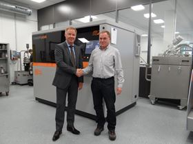Harald Henkel, MD of FKM Sintertechnik GmbH, and Oliver Edelmann, vice president sales and marketing at Concept Laser GmbH, in front of a laser sintering machine.