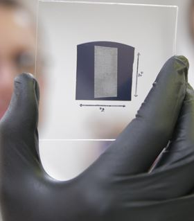 The UW-Madison engineers use a solution process to deposit aligned arrays of CNTs onto 1-in. square substrates. The researchers used their scalable and rapid deposition process to coat the entire surface of this substrate with aligned carbon nanotubes in less than five minutes. The teams breakthrough could pave the way for CNT transistors to replace Sitransistors, particularly in wireless communications technologies. Photo credit: Stephanie Precourt, UW-Madison College of Engineering.