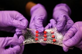 A sheet of hydrogel is bonded to a matrix of polymer islands (red) that can encapsulate electronic components such as semiconductor chips, LED lights and temperature sensors. Photo: Melanie Gonick/MIT.