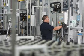 A GKN Driveline employee processes a propshaft utilizing a crimping operation.
