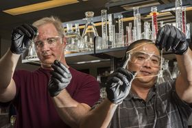 Sandia National Laboratories researchers Cy Fujimoto (right) and Michael Hibbs (left) demonstrate the clarity of their recent membranes. Photo: Randy Montoya, Sandia National Laboratories.