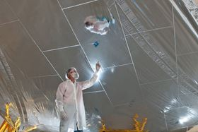 A NASA engineer in a cleanroom looks at one of the sunshield layers with a grid pattern of rip-stops. Photo: Nexvolve.