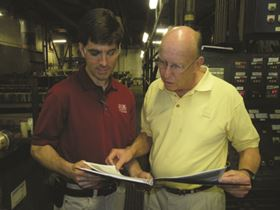 Chris Henderson (left) information manager, and Jim Jones, vice president, review reports from one of Dixie Industrial Finishing's rack lines.