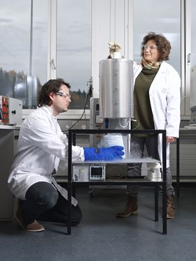 PSI researchers Mickaël Morin and Marisa Medarde freeze-in the atomic arrangement of the multiferroic material YBaCuFeO5. The material is first heated in an oven to 1000°C and then dropped into a vessel filled with liquid nitrogen at a temperature of -200°C. (Photo: Paul Scherrer Institute/Markus Fischer).