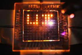 A laser stylus writes on a small array of multifunction pixels made from nanorod LEDs that can both emit and respond to light. Image: Moonsub Shim, University of Illinois.