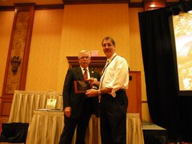 NASF president Tony Revier (left) presents Award of Merit to Art Brooks, KCH Engineered Systems.