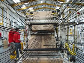 Tows of UD reinforcements are fed into machinery in the prepreg production process at this ACG facility.