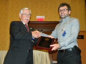 NASF's Revier (left) presents Award of Merit to Graham Torr, Haviland USA.