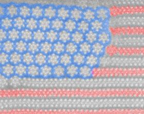 This tiny US flag is created from molybdenum ditelluride stars and stripes. Image: University of Texas at Dallas.
