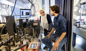 Joint first authors Elham Fadaly (left) and Alain Dijkstra (right) operating an optical setup to measure the light emitted by the hexagonal silicon-germanium alloy. Photo: Sicco van Grieken, SURF.