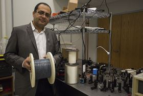 Ayman Abouraddy with a roll of multi-layered fiber. Photo: UCF.