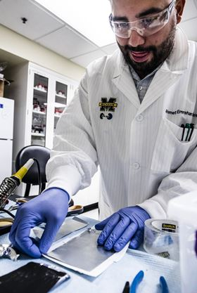 Ahmet Emrehan Emre, a biomedical engineering PhD candidate at the University of Michigan, sandwiches a thin sheet of a cartilage-like material between a layer of zinc on top and a layer of manganese oxide beneath to form a battery. Photo: Evan Dougherty/Michigan Engineering.