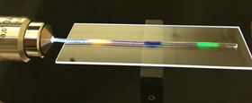 MIT researchers have developed a stretchy optical fiber in which they injected multiple organic dyes (yellow, blue and green regions). In addition to lighting up, the dyes act as a strain sensor, allowing the researchers to quantify where and by how much the fiber has been stretched. Photo courtesy of the researchers.