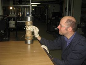 An Element Hitchin scientist inspects a reinforced thermoplastic pipe following burst testing.