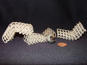Three 3D-printed soft, flexible scaffolds: those on the outside are maintained in rigid, bent positions via cooled, rigid wax coatings, while the one in the middle is uncoated and remains compliant (here, it collapses under a wrench).