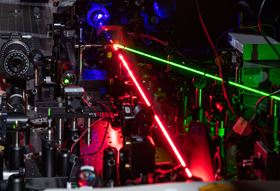 This photo shows a red laser creating nonlinear effects with tiny triangles of gold. The blue beam shows the frequency-doubled light and the green beam controls the migration of the excited electrons. Photo: Rob Felt, Georgia Tech.