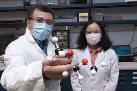Brookhaven chemists Enyuan Hu (left) and Zulipiya Shadike (right) with a model of 1,2-dimethoxyethane, a solvent used in lithium-metal battery electrolytes. Photo: Brookhaven National Laboratory.