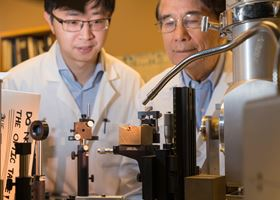 Liangzi Deng (left) and Paul Chu (right) from the University of Houston examine a miniature diamond anvil cell (mini-DAC), which is used to measure superconductivity. Photo: Audrius Brazdeikis.