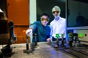Adrian Sabau and Jian Chen work with a laser to prepare the surface of carbon fiber composites and aluminum.