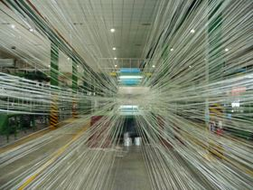 Glass roving being processed into unidirectional prepreg for the wind energy market at Guang Wei Composites' facility.