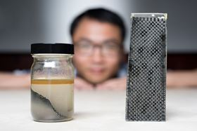 Kai Yu, a former postdoctoral researcher in The George W. Woodruff School of Mechanical Engineering at Georgia Tec, sits behind a piece of carbon fiber composite immersed in alcohol. (Credit: Rob Felt, Georgia Tech).