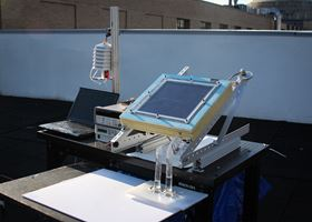 A prototype of the new two-stage water harvesting system was tested on a rooftop at MIT. The device, which was connected to a laptop for data collection and mounted at an angle to face the sun, has a black solar-collecting plate at the top. The water it produced flowed into two tubes at the bottom. Photo: Alina LaPotin.