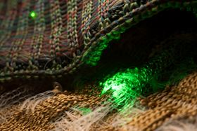 This photo shows how the novel fibers with embedded electronics can be woven into soft fabrics and made into wearable clothing. Photo courtesy of the researchers.