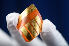 A researcher at Georgia Tech holds a perovskite-based solar cell, which is flexible and lighter than silicon-based versions. Photo: Rob Felt, Georgia Tech.