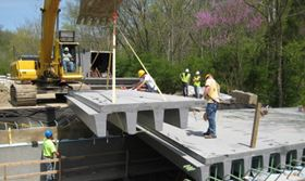 In addition to lighter weight, corrosion resistance, higher strength and lower life cycle costs, FRP technology offers faster installation. Prefabricated FRP panels can be installed quickly, compared to the labour intensive process of erecting formwork, placing rebar, pouring and curing concrete, and removing the formwork needed to construct a cast-in-place bridge.  Eliminating the need for heavy equipment, FRP panels are generally placed starting at one abutment with light equipment such as an excavator.