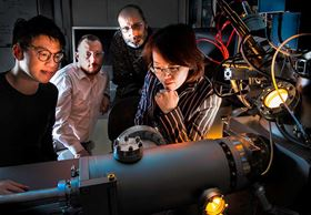 NREL researchers (left to right) Seoung-Bum Son, Steve Harvey, Andrew Norman and Chunmei Ban working with a time-of-flight secondary ion mass spectrometer, which allows them to investigate material degradation and failure mechanisms at the micro- to nano-scale. Photo: Dennis Schroeder / NREL.