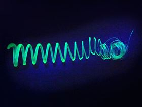This shows an extruded spiral made of polymer-coated silicon-nanosheets glowing in UV light. Photo: Tobias Helbich/TUM.