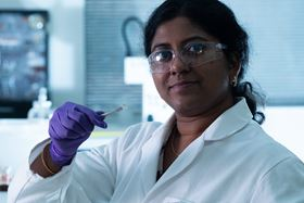 Rice University postdoctoral fellow Anulekha Haridas holds a full-cell lithium-ion battery built to test the effect of an alumina coating on the cathode. The nanoscale coating protects cathodes from degrading. Photo: Jeff Fitlow/Rice University.