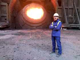 Dr Szymon Kubal next to a molten steel ladle.