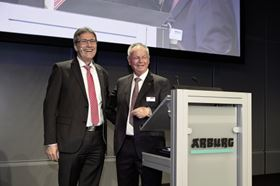During the farewell celebration, Partner Eugen Hehl presents Herbert Kraibühler with the Arburg logo in gold.