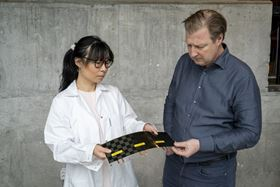 Johanna Xu (left) and Leif Asp (right) from Chalmers University of Technology examine a newly manufactured structural battery cell. Photo: Marcus Folino, Chalmers University of Technology.