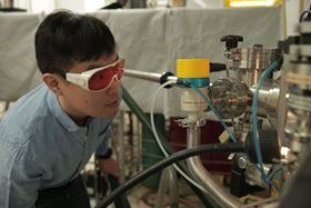 Hyungwoo Lee, a materials science and engineering postdoctoral researcher at the University of Wisconsin-Madison, looks inside a thin film deposition system during growth of an oxide thin film structure. Image: Renee Meiller.