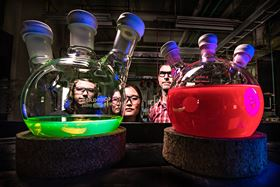 NREL's Ashley Marshall, Erin Sanehira and Joey Luther with solutions of the all-inorganic perovskite quantum dots, showing intense photoluminescence when illuminated with UV light. Photo: NREL.