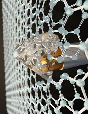 By applying pressure at the nanoscale with an indenter to two layers of graphene, each one-atom thick, CUNY researchers transformed honeycombed graphene into a diamond-like material at room temperature. Image: Ella Maru Studio.