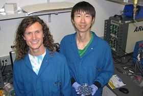 "Stanford PhD students David Mackanic (left) and Zhiao Yu (right) with their battery tester at right. Yu holds a dish of already tested cells that they call ""the battery graveyard"". Photo: Mark Golden."
