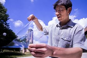 Jay Guo holds a sheet of the flexible transparent conductor, in which a thin layer of silver is sandwiched between two dielectric materials, aluminum oxide and zinc oxide, to produce a conductive anti-reflection coating on a sheet of plastic. Image: Robert Coelius/University of Michigan Engineering, Communications & Marketing.