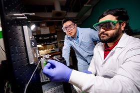 Bruce Lee (left) and Saleh Akram Bhuiyan (right) use a thin platinum wire to deliver a jolt of electricity to a catechol-containing adhesive on a titanium sphere. Photo: Sarah Bird/Michigan Tech.