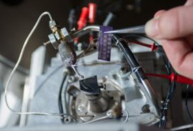 This image shows a heated capillary micro-nozzle installed on the deposition stage of an FEBID system, along with the test chip used for electrical characterization of deposits for graphene interconnects. (Georgia Tech Photo: Rob Felt)
