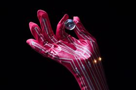 Each fingertip pressure sensor mounted on this glove is connected to an LED; the intensity of the light emitted by the LED varies in accordance with the pressure applied by the fingertips. Photo: 2017 Someya Group, The University of Tokyo.