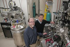 Chang-Beom Eom (right) and Mark Rzchowski (left) inspect a materials growth chamber. The researchers have made a new material that can be switched from electrical conductor to insulator. Photo: UW-Madison photo by Sam Million-Weaver.