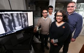 Iowa State University researchers (left to right: Metin Uz, Suprem Das, Surya Mallapragada and Jonathan Claussen) are developing technologies to promote nerve regrowth. The monitor shows mesenchymal stem cells (white) aligned along graphene circuits (black). Photo: Christopher Gannon/Iowa State University.